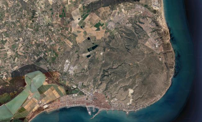 Vista aérea de la sierra de Santa Pola (atolón del Cabo); al sur: municipio y puerto, al norte: urbanizaciones de Gran Alacant; se aprecia carretera recta de la nacional al faro, ca. 1944 (Google)